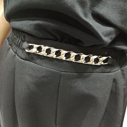 pantalon negro bolsillos laterales y detalle cadena en cintura lleva goma en el puño del tobillo